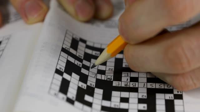 brain training - hand doing crossword puzzle closeup