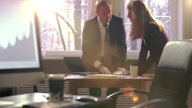 Brainstorming. Collègues homme et femme émotionnellement discuter des plans d'affaires dans un bureau. Optique évasé de soleil. Au ralenti. - Vidéo