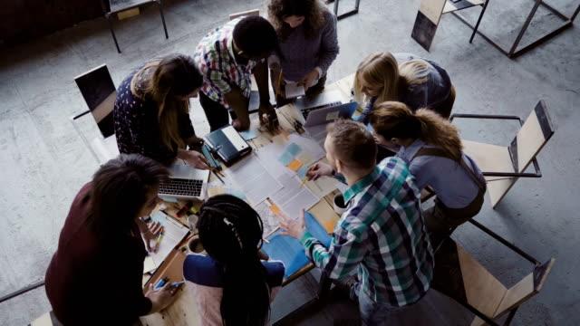 vidéos et rushes de remue-méninges si créatif mixte groupe course de personnes au bureau moderne. vue de dessus du groupe de personnes debout près de table - communion