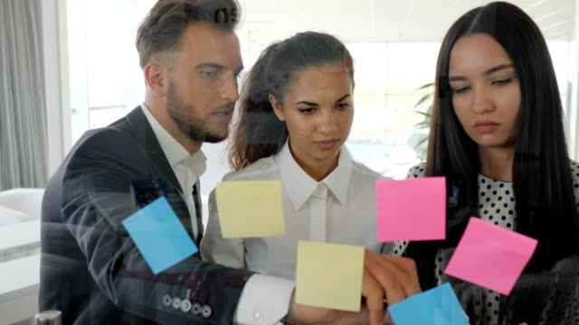 brainstorming, workers looking at glass wall planner with notes in boardroom, young business team writing down ideas on sticky video