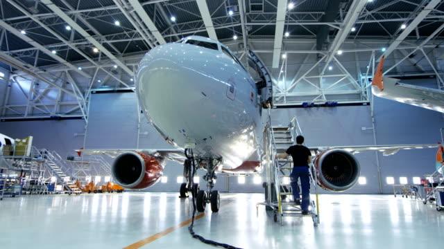 새로운 비행기 항공기 유지 보수 엔지니어 동안 항공기 정비 격납고에 서 브랜드 / 기술자 사다리를 통해 객실 내부 수리가 / 램프 /. - 항공 비행체 스톡 비디오 및 b-롤 화면