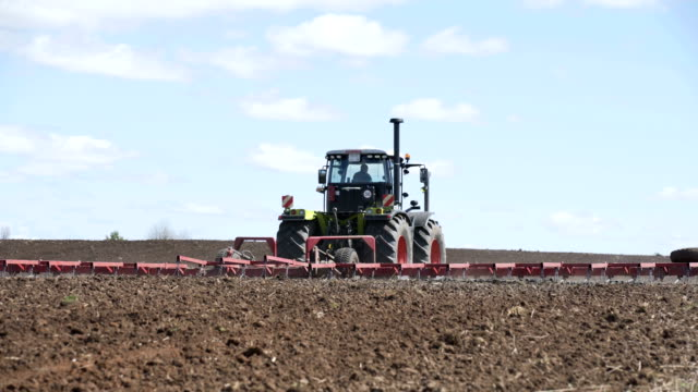 Brand new tractor on field working. Tractor plowing land. Tractor cultivating field - video