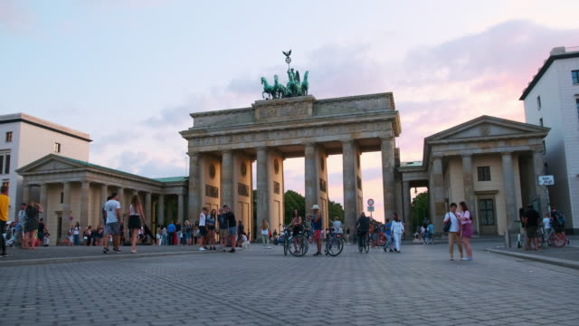 brandenburg gate and tourists walking around it at sunset - stabilized shot стоковые видео и кадры b-roll