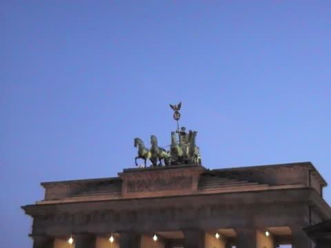 brandenburg gate in der dämmerung - pferdeartige stock-videos und b-roll-filmmaterial