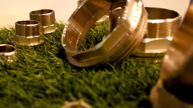Brass and plastic plumbing parts on the surface of artificial grass Brass and plastic plumbing parts on the surface of artificial grass. Shot in motion. Closeup. Dolly shot. Shallow depth of field. Rack focus pipe connector stock videos & royalty-free footage