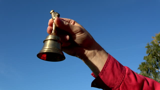 Brass bell in hand on sky background video