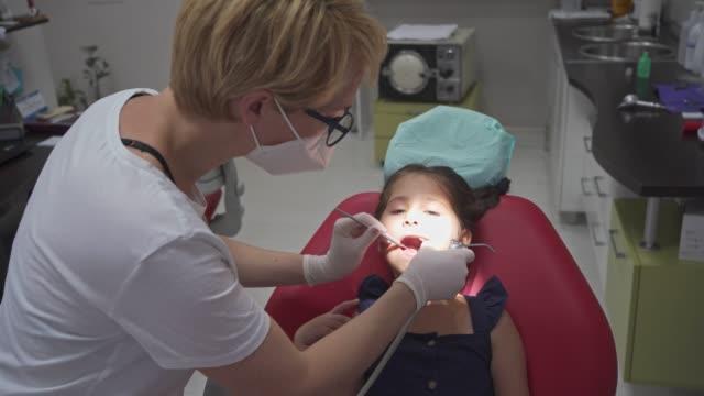 vídeos y material grabado en eventos de stock de valiente chica de 5 años sentada en la silla del dentista durante su chequeo mensual - ortodoncista