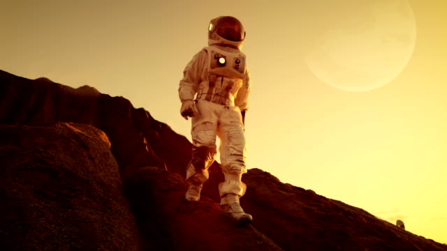 brave astronaut descents from the mountain on the alien red planet/ mars. space exploration/ travel, colonization concept. - coraggio video stock e b–roll