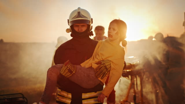 brave firefighter carries injured young girl to safety. in the background car crash traffice accident with courageous paramedics and firemen save lifes, fight fire - paramedic stock videos & royalty-free footage