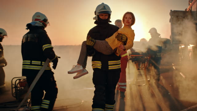 Brave Firefighter Carries Injured Young Girl to Safety where She Reunited with Her Loving Mother. In the Background Car Crash Traffic Accident Courageous Paramedics and Firemen Save Lives Brave Firefighter Carries Injured Young Girl to Safety where She Reunited with Her Loving Mother. In the Background Car Crash Traffic Accident Courageous Paramedics and Firemen Save Lives rescue worker stock videos & royalty-free footage
