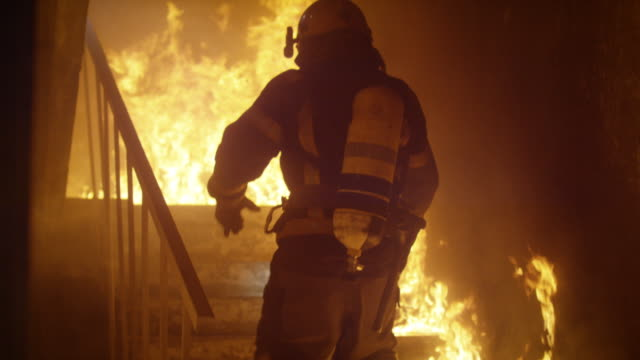vídeos de stock e filmes b-roll de brave firefighter runs up the stairs. in slow motion. raging fire is seen everywhere. - resgate