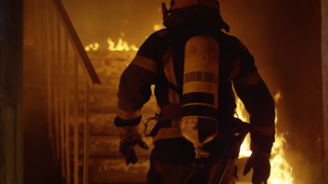 brave firefighter runs up the stairs. raging fire is seen everywhere. - firefighter stock videos and b-roll footage
