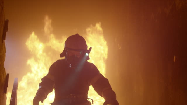 Brave Firefighter With Switched On Flashlight on His Helmet Runs Down the Burning Stairs. Fire is Raging. In Slow Motion. video
