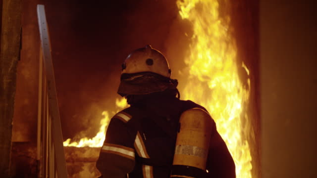 Brave Fireman Ascends on Burning Stairs. Looking Around Inspecting Building. Open Flames in the Background. - Vidéo