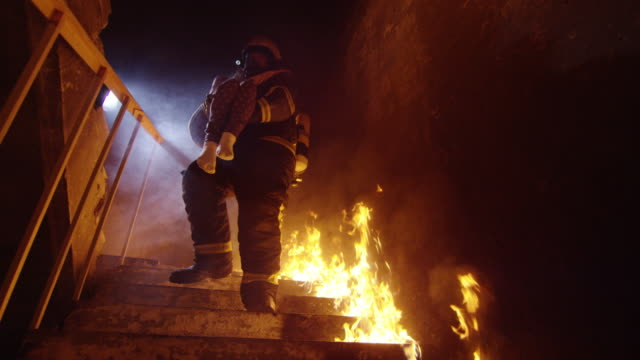 vídeos de stock e filmes b-roll de brave fireman descends burning stairs with saved little girl in his hands. open flames are seen everywhere. - resgate