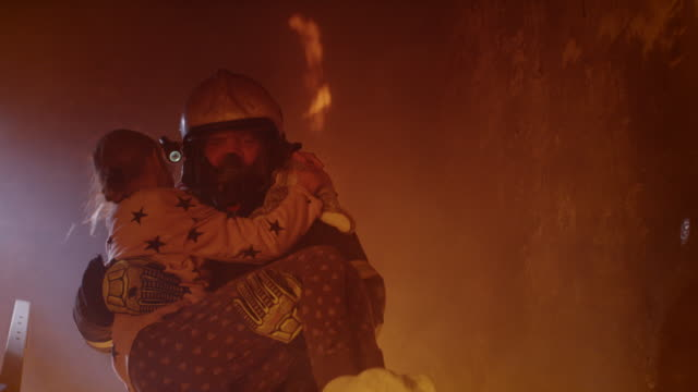 vídeos de stock e filmes b-roll de brave fireman descends stairs of a burning building with a saved girl in his arms. - resgate