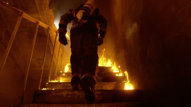 Brave Fireman Runs Up the Burning Stairs. Fire is Everywhere. In Slow Motion. video