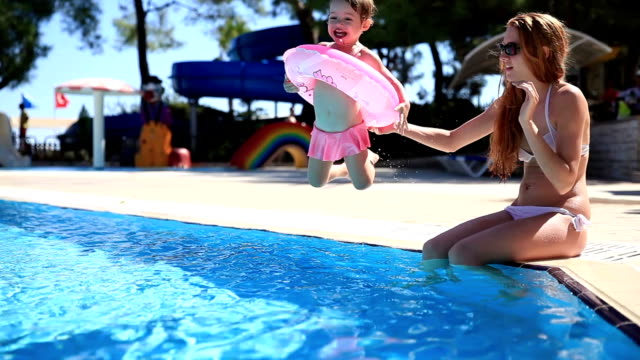 Brave little girl having fun jumping into the pool with pink lifeline. video