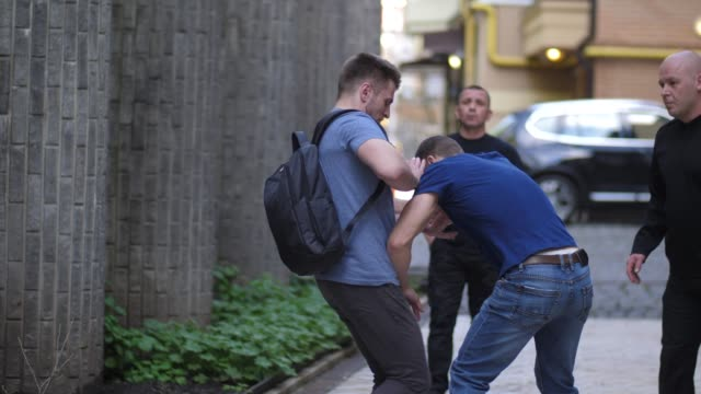 brave man fighting with muggers on deserted lane - colpire con un pugno video stock e b–roll
