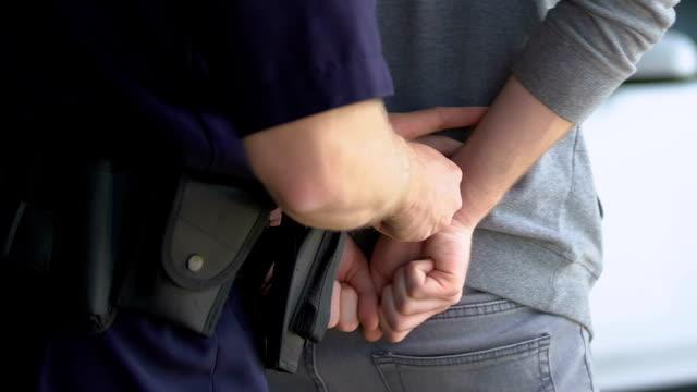 храбрый офицер надел наручники на задержанного преступника и отвехивал его в машину - арест стоковые видео и кадры b-roll