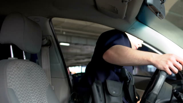 Brave police officer getting into car and wearing sunglasses, city patrolling