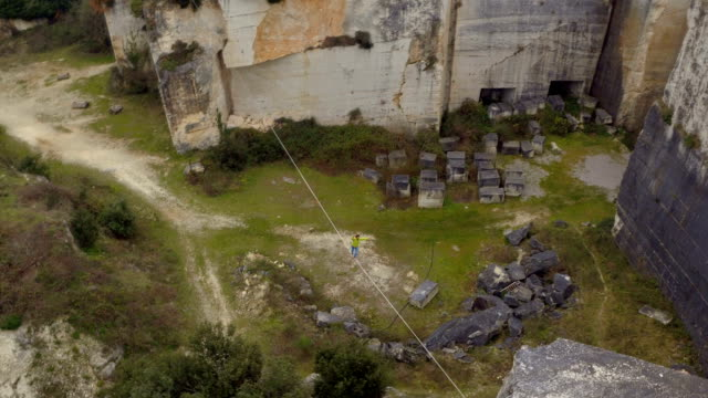 AERIAL: Brave young man slacklining on challenging highline over deep abyss video