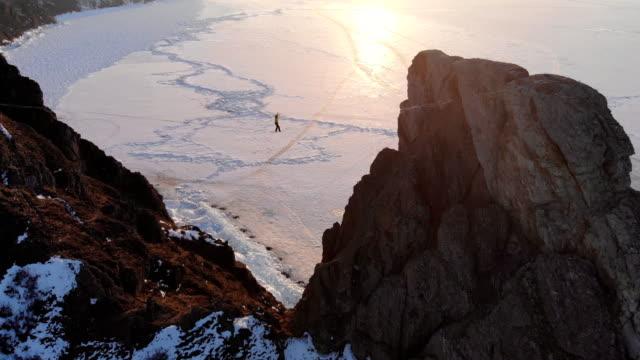 vídeos de stock e filmes b-roll de brave young woman walking on a sling on a high rock. - lago baikal