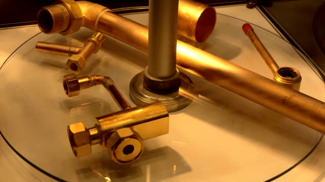 Brazed pipe joints Brazed copper and brass metal pipe joint samples are revolving on display shelve pipe connector stock videos & royalty-free footage
