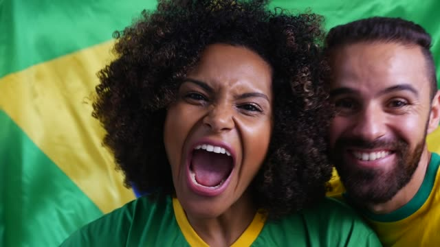 vídeos de stock e filmes b-roll de brazilian couple cheering with brazilian flag in the background - soccer supporter portrait