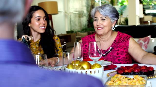 brazilian family celebrating christmas dinner - pranzo di natale video stock e b–roll