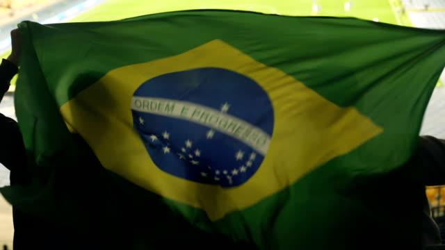 Família brasileira com criança acenando a bandeira nacional, torcendo para time de futebol - vídeo