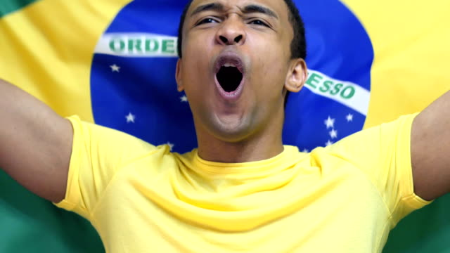 Brazilian Fan Celebrates holding the flag of Brazil in Slow Motion video