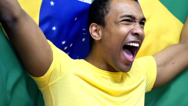 Brazilian Fan Celebrating while holding the flag of Brazil in Slow Motion video