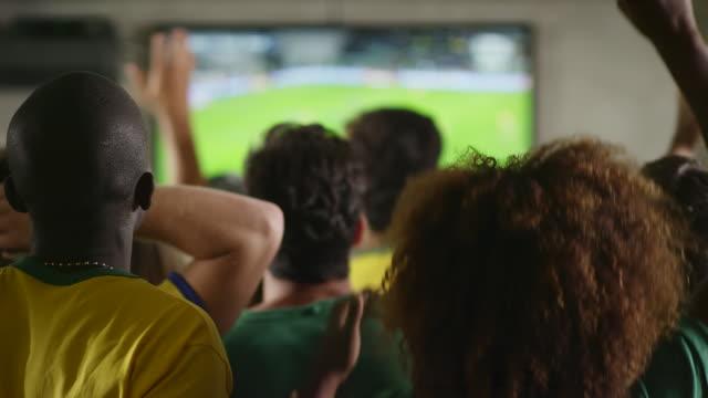 ブラジルファンのサッカーの試合観戦、スポーツバー - 注視する点の映像素材/bロール