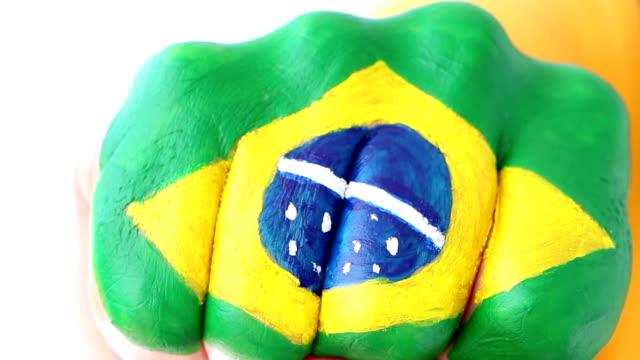 vídeos de stock, filmes e b-roll de fã de futebol brasileiro futebol fazendo gesto vencedor, bandeira brasileira - campeonato esportivo