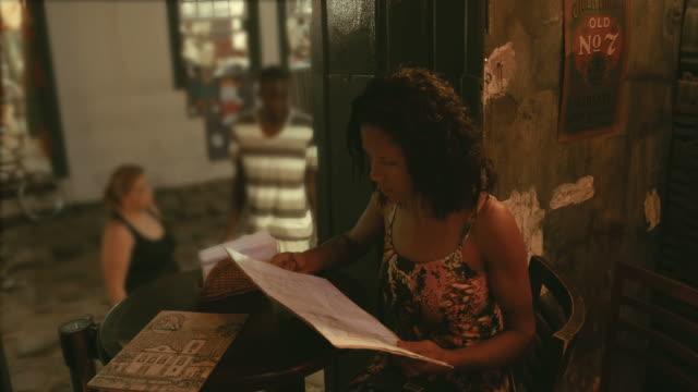 Brazilian girl looking at menu at a cocktail bar Brazilian girl looking at menu at a cocktail bar,,,,. menu stock videos & royalty-free footage