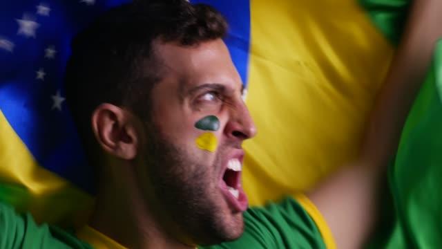 Cara brasileira, celebrando com a bandeira do Brasil - vídeo