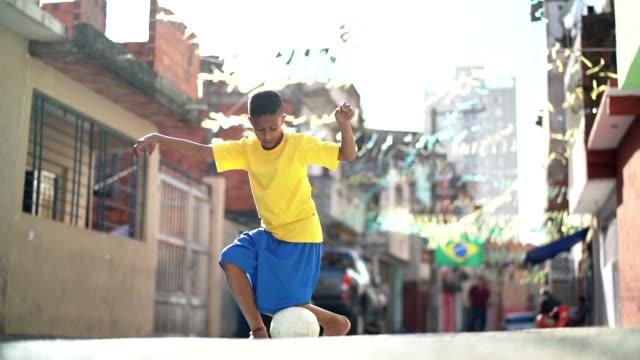 Garoto brasileiro jogando futebol na rua - vídeo