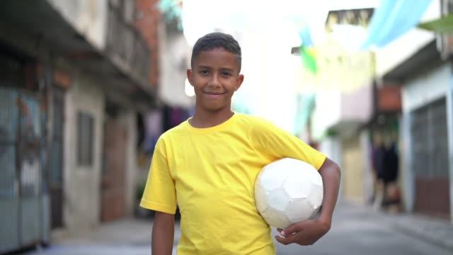 vídeos de stock e filmes b-roll de brazilian kid playing soccer portrait - soccer supporter portrait