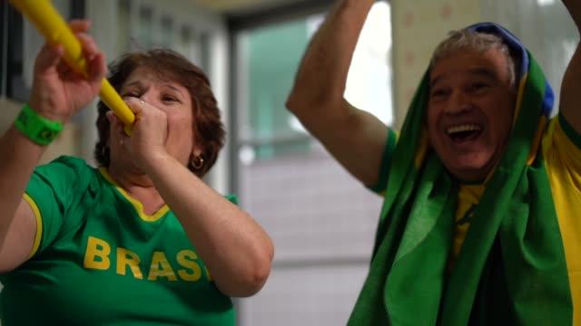 Fã brasileiro sênior casal assistindo jogo de futebol em casa - vídeo
