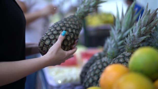 donna brasiliana che acquista frutta sul mercato di strada - mercato frutta donna video stock e b–roll