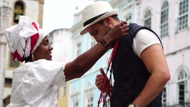 vídeos y material grabado en eventos de stock de mujer brasileña dando su collar al turismo en salvador, bahía - viaje a sudamérica