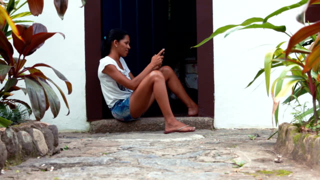 Brazilian woman sitting at house entrance video
