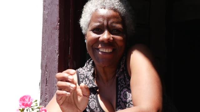 オウロ ・ プレット、ミナスジェ ライス州、ブラジルの典型的な家のウィンドウでブラジルの女性の笑顔 - ブラジル文化点の映像素材/bロール