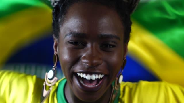 vídeos de stock e filmes b-roll de brazilian young black woman celebrating with brazil flag - soccer supporter portrait