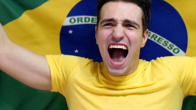 Brazilian Young Man Celebrates holding the flag of Brazil in Slow Motion video
