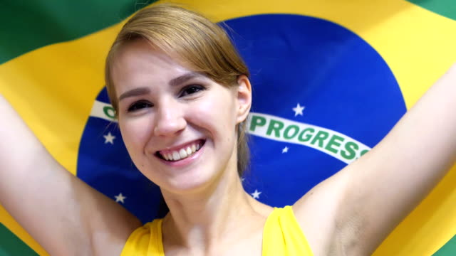 Brazilian Young Woman Celebrating while holding the flag of Brazil in Slow Motion video