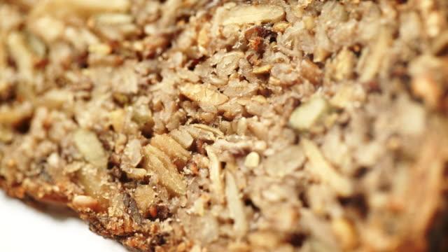 vídeos de stock, filmes e b-roll de fundo do pão com sementes e porcas, dolly disparou 4k - sem glúten
