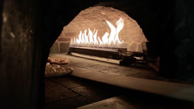 bread inside the oven,removing bread from brick oven,pitta bread,turkish pizza pita inside the oven - chleb pita filmów i materiałów b-roll