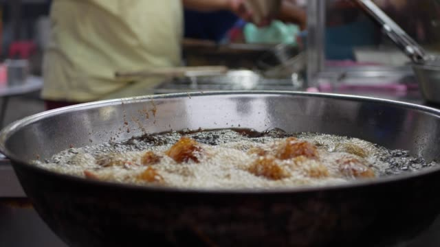 Breaded chicken cooking in a deep fryer full of hot, bubbling vegetable oil in wok at street local market. 4k